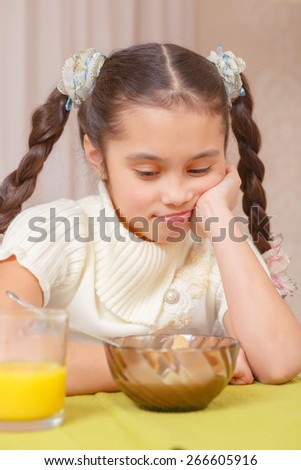 No appetite. Portrait of a small girl with brown hair looking sadly on her plate as if not willing to finish her meal - stock photo