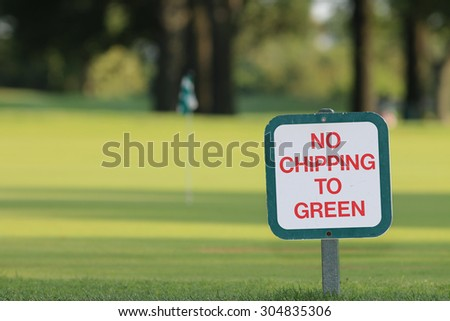 No Chipping to Green Golf Course Sign Positioned near Green, with A Golf Cart in the Background. - stock photo