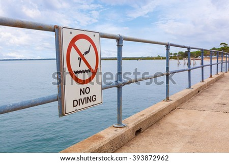 No Diving sign on a pier railing with ocean water in the background - stock photo