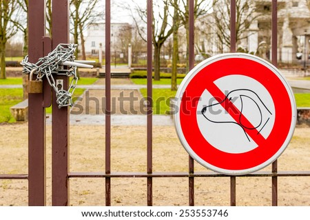 No dogs allowed sign and locked park gate - stock photo