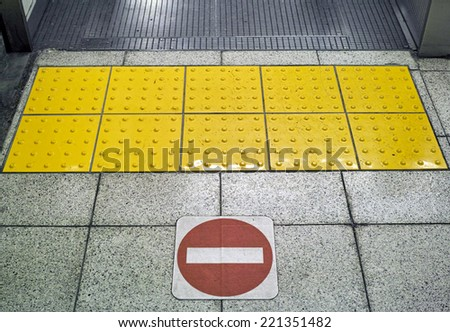 No entry symbol and yellow studded paving block (braille block) for the blind person, photographed in Tokyo, Japan. - stock photo