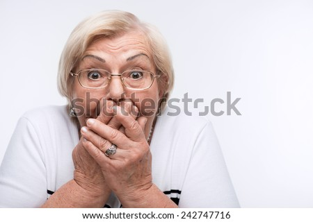 No evil. Pretty elderly woman covering her mouth with hands and gesturing three wise monkeys while standing over white background - stock photo