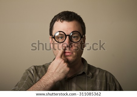 no expression at all a guy with glasses picks his nose - stock photo