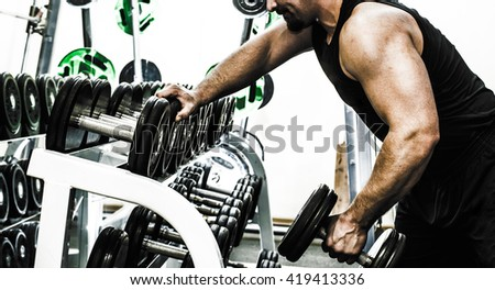 no face. Unrecognizable beard person. muscular torso man with dumbbell on gray background in studio gym background . Bodybuilder working out biceps with dumbbell Male wear black sport closes - stock photo