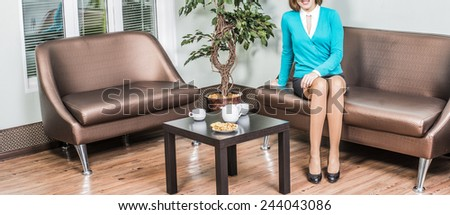 No face Unrecognizable cute woman Beautiful alone girl is sitting in dark leather brown sofa in cafe room near black wooden table with white cookies plate kettle tea or coffee cup for two person  - stock photo