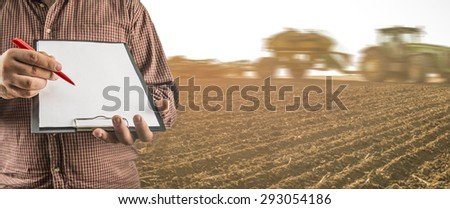No face Unrecognizable person Businessman hold empty list of paper pen Business man wear brown shirt Copy space for inscription Experienced agronomist examining spring meadow in field Takes readings - stock photo