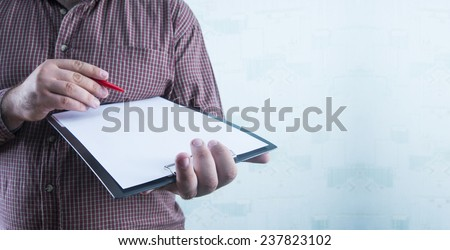 No face Unrecognizable person Businessman holding white texture empty list of paper and red pen Business man wearing stripped brown shirt Copy space for inscription on wallpaper structure - stock photo