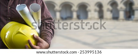 No face Unrecognizable person construction worker man holding in hands blueprint and yellow helmet on stone building arch and floor in perspective background Empty copy space for inscription - stock photo