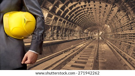 no face unrecognizable person engineer hand holding yellow helmet for workers security against the background of an underground mine with arc legs and rails for trolleys with coal in perspective - stock photo
