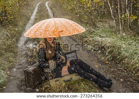 No face Unrecognizable person girl under orange snowy umbrella, late autumn Adult woman sit in open old retro vintage aged suitcase on land way road between green and yellow grass field with trees - stock photo