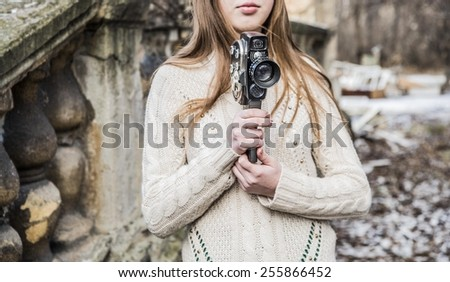 No face Unrecognizable person Outdoor of beautiful  woman with brown long hair holding vintage 8mm camera in hands Outdoor cute girl in winter snowy park near on old retro vintage aged concrete fence - stock photo