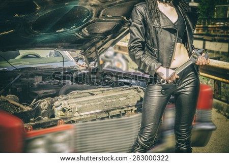 No face Unrecognizable person sexy young woman holding metal wrench standing by an open hoof of old retro vintage aged used car Empty space for inscription Idea of repairing auto