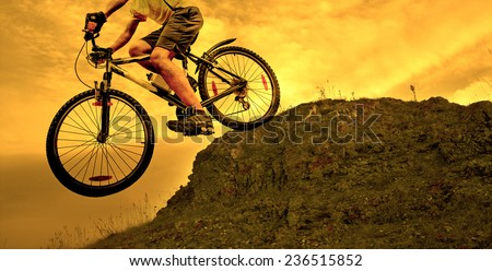 no face Unrecognizable person Silhouette of a man on mountain bike jumping in air on big stone  against sunset yellow sky with dramatic clouds background texture Empty copy space for inscription - stock photo