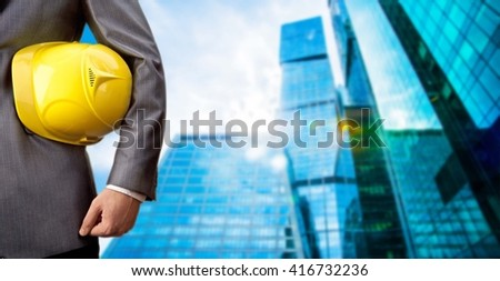 No face Unrecognizable person. torso of engineer or worker hold in hand yellow helmet for workers security on skyscraper background. Man wear business suit and white shirt  - stock photo