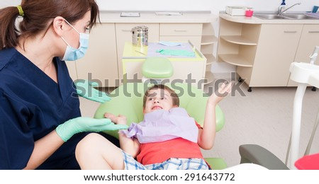 No fear of dentist concept with relaxed kid or child and friendly woman doctor - stock photo