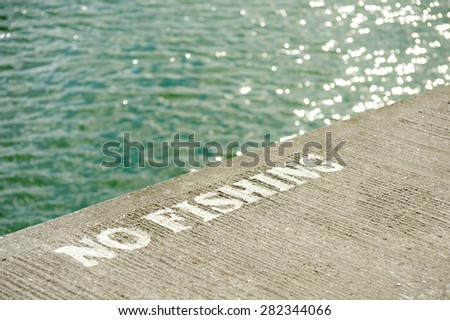 no fishing sign of the edge of a concrete quayside - stock photo