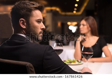 No more words. Thoughtful young couple sitting at the restaurant and looking away - stock photo