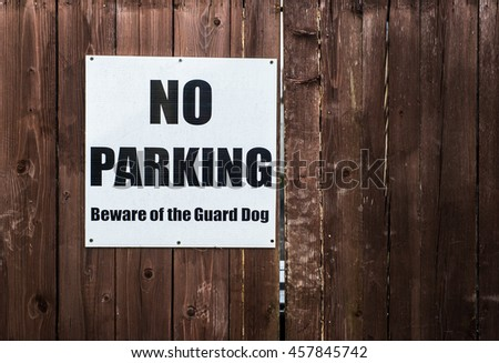 No parking and beware of guard dog sign on wooden gate - stock photo