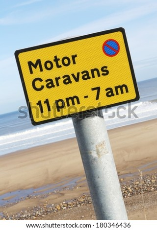 No parking for motor caravans between 11pm and 7am warning sign against a coastal background.