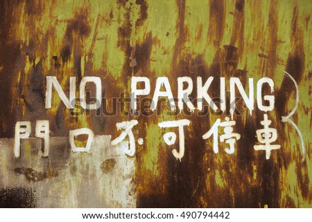 No parking inscription (in english and chinese) on a rusty metal door