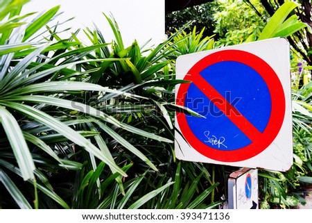 No Parking roadsign in front of tropical plants. - stock photo