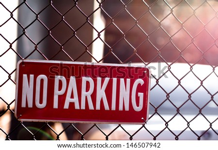No Parking Sign on Fence with Depth of Field and Sun Flair in Top Right Corner - stock photo