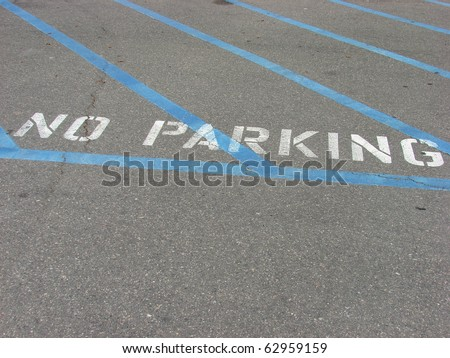 no parking sign on parking lot pavement - stock photo
