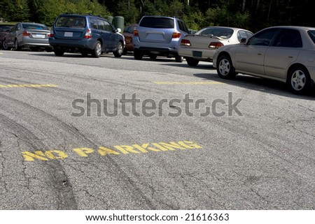 No parking text on road with cars in the back - stock photo