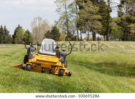 No person on expansive lawn with a yellow zero-turn mower - stock photo