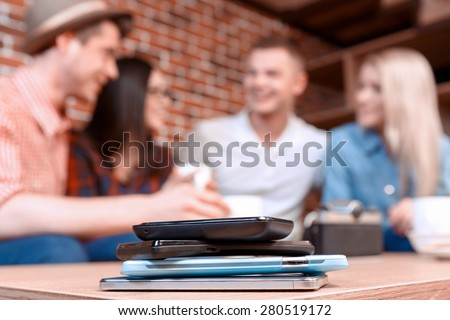 No phones party. Selective focus on mobile phones lying on each other on the table and the company of young students having fun in a cafe while chatting - stock photo