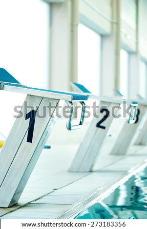 No. 1 starting block by the swimming pool, selective focus - stock photo