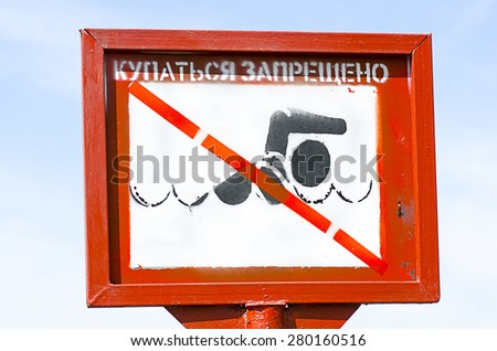 No swimming danger sign in Moscow, Russia on the shore sign against blue sky. on Russian language. - stock photo