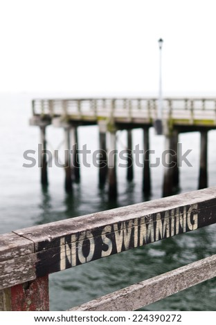 No-swimming sign on the fence of a pier in Coney Island, New York. - stock photo