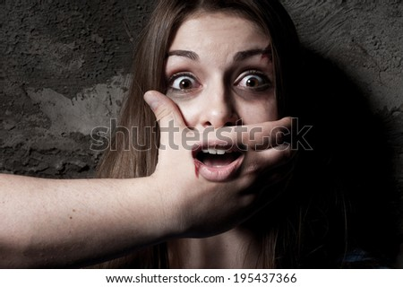 No! Terrified young woman with hand covering her mouth staring at camera - stock photo