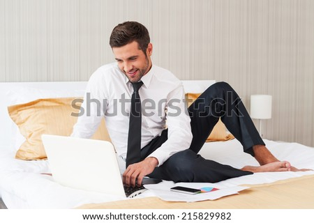 No time for rest. Handsome young man in shirt and tie working on laptop and smiling while sitting in bed at the hotel room  - stock photo