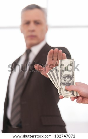 No to bribing. Confident grey hair businessman gesturing stop sign while someone proposing money to him  - stock photo