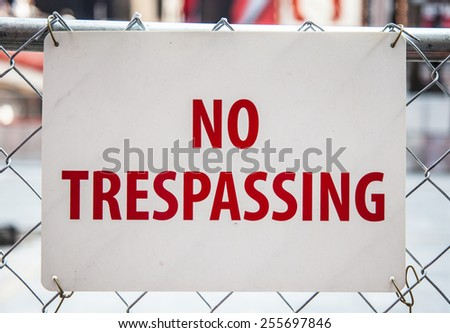 No trespassing sign hanging on fence - stock photo