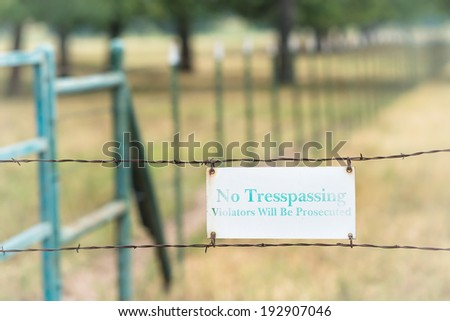 No tresspassing sign attached on a barbed wire fence - stock photo