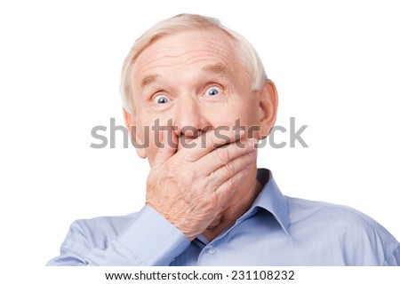 No way! Excited senior man formalwear covering mouth with hand and looking at camera while standing against white background  - stock photo