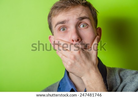 No way! Shocked young man covering mouth with hands and looking at camera  - stock photo