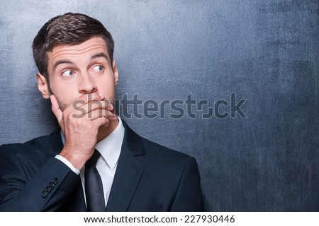 No way! Shocked young man in formalwear covering mouth with hand and looking away while standing against blackboard  - stock photo