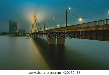 Nocturnal view on cable bridge and left bank of Daugava river in center of Riga - capital and largest city of Latvia, major commercial, cultural, historical and financial center of the Baltic region