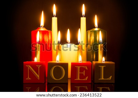 NOEL candles against a black background. - stock photo