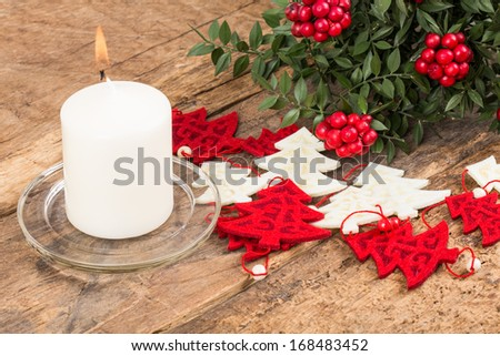 noel decoration and candle on wooden surface - stock photo