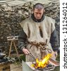 NOGENT LE ROTROU,FRANCE,MAY19 :Environmental portrait of a medieval blacksmith working on fire during a medieval reenactment festival around St. Jean Castle on May 19 2012 in Nogent le Rotrou, France. - stock photo