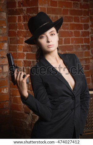 Noir film style woman in a black suit posing with a gun