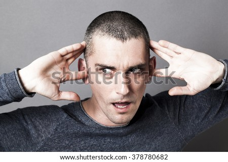 noise and hearing concept - surprised young man plugging his ears to refuse listening to problems or noise, contrast effects