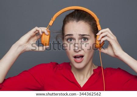 noisy headphones concept - beautiful 20s girl listening to loud music with earphones on,removing her earphones to avoid tinnitus,studio shot - stock photo