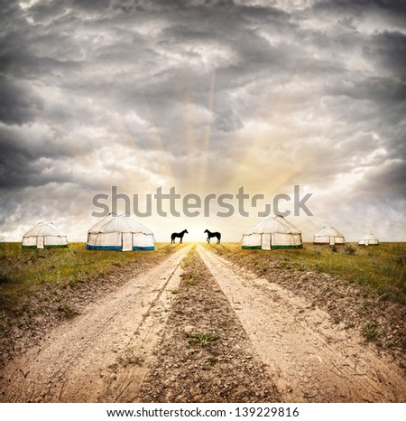 Nomadic village with yurts and horses at dramatic overcast sky with sun in steppe in Asia - stock photo