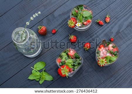 Non-alcoholic mojito strawberry cocktail on the dark wooden table, top view - stock photo